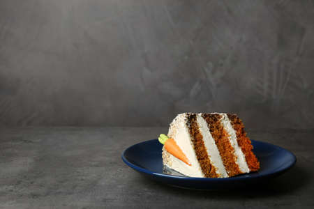 Plate with piece of carrot cake on grey table, space for text