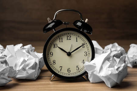 Crumpled paper balls and alarm clock on wooden table Imagens