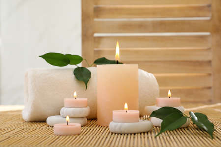 Composition of spa stones, towel and burning candles on bamboo mat