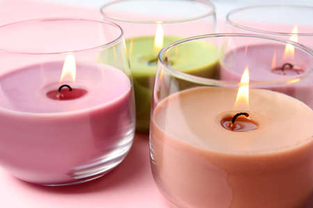 Burning wax candles in glass holders on pink background, closeup