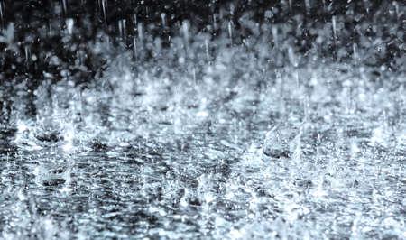 Fuertes lluvias cayendo sobre el suelo contra un fondo oscuro