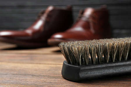 Shoe brush and leather footwear on wooden surface, space for text Stock Photo