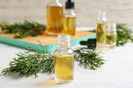 Composition with bottle of conifer essential oil on white wooden table
