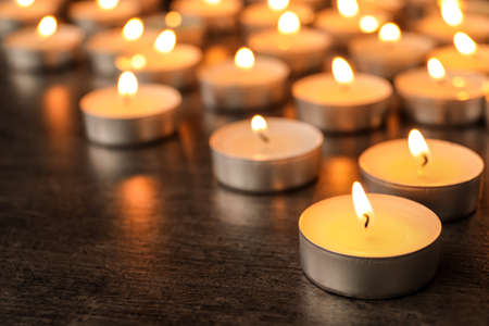 Burning candles on wooden table, space for text. Symbol of sorrow Stock Photo