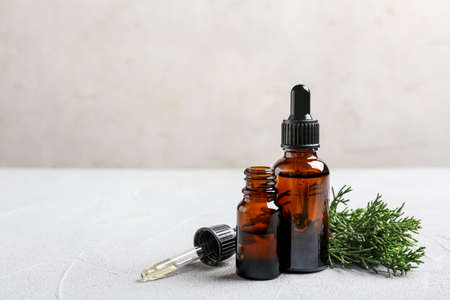 Composition with bottles of conifer essential oil on light table. Space for text Stock Photo