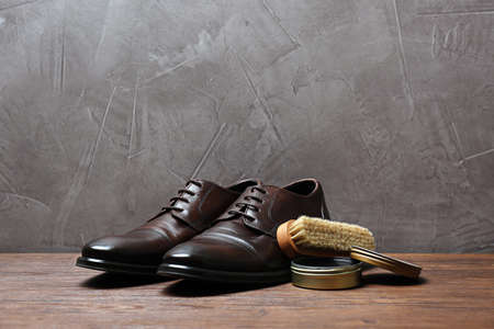 Leather footwear and shoe shine kit on wooden surface, space for text