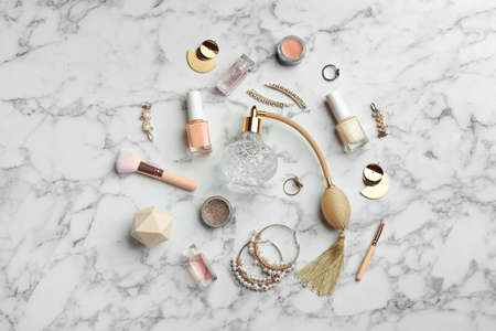 Flat lay composition with perfume bottles, jewelry and decorative cosmetics on white marble table