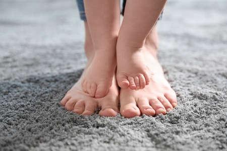 Bebé dando los primeros pasos con la ayuda de la madre, primer plano
