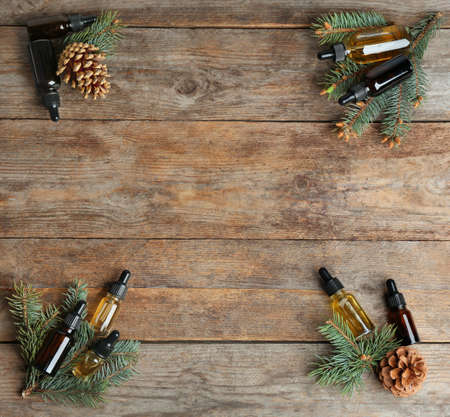 Flat lay composition with bottles of conifer essential oil and space for text on wooden background Stock Photo