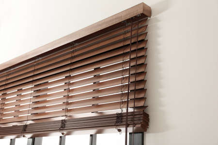 Modernes Fenster mit stilvollen Holzjalousien im Innenbereich Standard-Bild