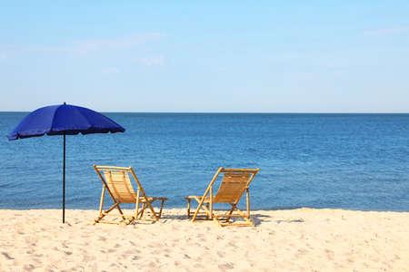 Empty wooden sunbeds and umbrella on sandy shore. Beach accessories Reklamní fotografie