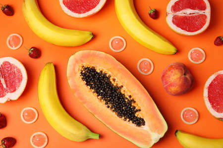Flat lay composition with condoms and exotic fruits on orange background. Erotic concept