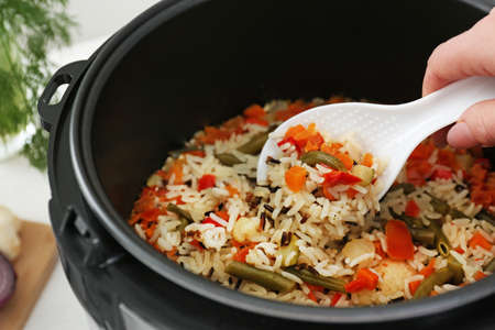 Woman preparing rice with vegetables in multi cooker, closeup