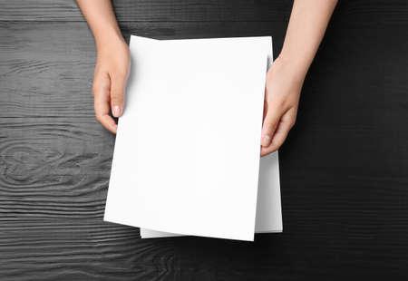 Mujer sosteniendo hojas de papel en blanco para folleto en la mesa de madera negra, vista superior. Bosquejo