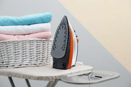 New modern iron and basket with laundry on board against color background 免版税图像