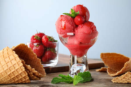 Delicious strawberry ice cream in dessert bowl on wooden table against light background