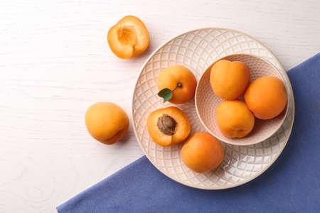 Zusammensetzung mit köstlichen Aprikosen auf weißem hölzernem Hintergrund, Draufsicht. Platz für Text Standard-Bild