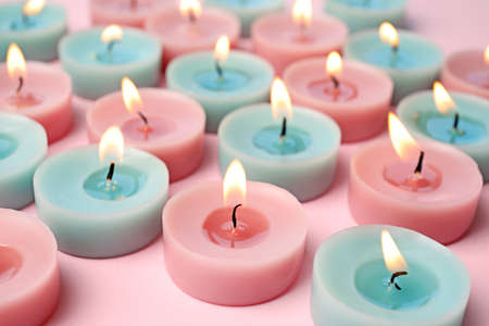 Burning colorful decorative candles on pink background, space for text