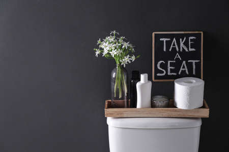Decor elements, necessities and toilet bowl near black wall, space for text. Bathroom interior Imagens