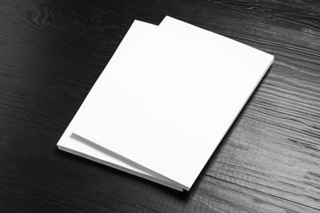 Stack of blank paper sheets for brochure on black wooden background. Mock up