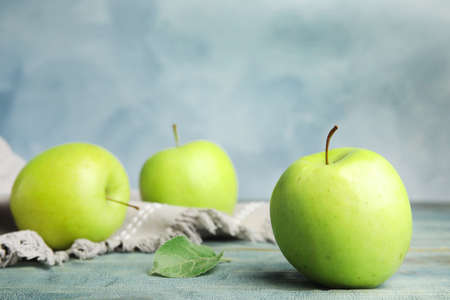 Fresh ripe green apples on wooden table against blue background, space for text
