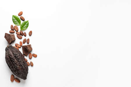 Cocoa pod with beans and chocolate pieces on white background, top view