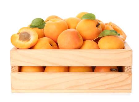 Caisse en bois de délicieux abricots sucrés mûrs isolés sur blanc