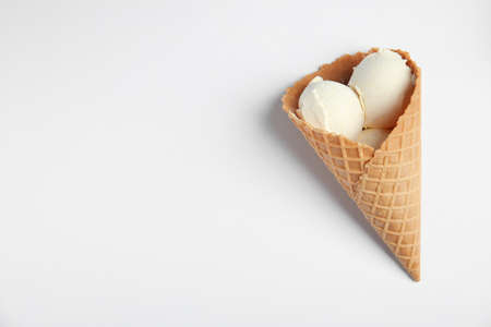 Delicious vanilla ice cream in wafer cone on white background, top view