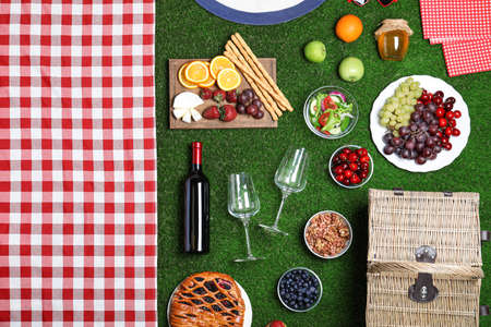 Flat lay composition with picnic basket and products on green grass