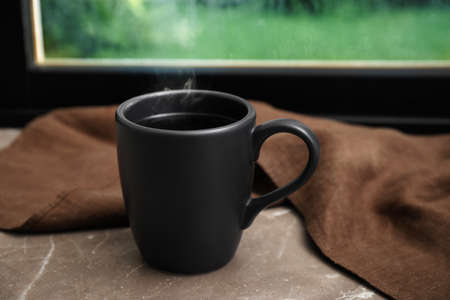 Tasse heißes Getränk auf grauer Marmorfensterbank