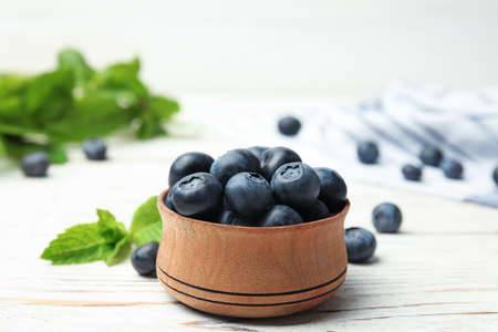 Wooden bowl with tasty blueberries on white table