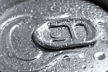 Aluminum can of beverage covered with water drops as background, closeup