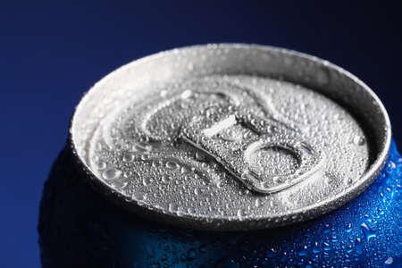 Lata de aluminio de bebida cubierta con gotas de agua sobre fondo azul, primer plano Foto de archivo