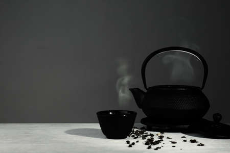 Oriental teapot and cup on table against grey background, space for text