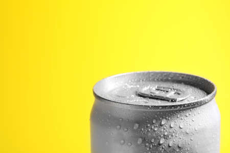 Aluminum can of beverage covered with water drops on yellow background, closeup. Space for text Фото со стока