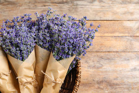 Fresh lavender flowers in basket on wooden table, top view. Space for text