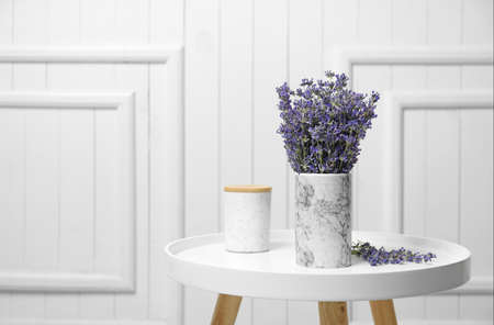 Fresh lavender flowers in vase on table against white wooden background, space for text