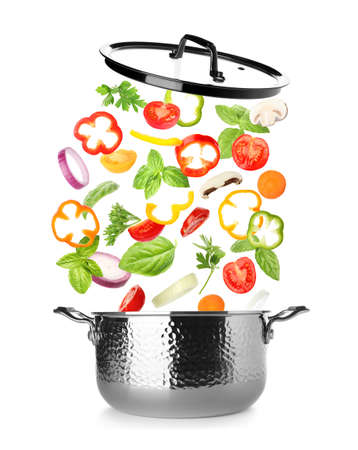 Many different ingredients falling into saucepan on white background. Recipe of delicious vegetable soup