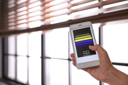 Femme utilisant une application de maison intelligente sur téléphone pour contrôler les stores à l'intérieur, en gros plan. Espace pour le texte Banque d'images