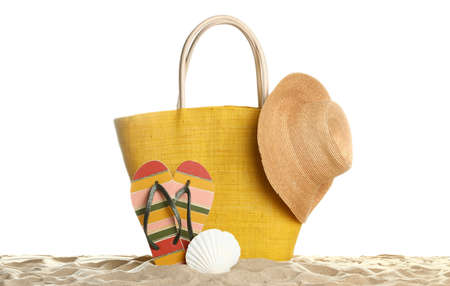 Stylish yellow bag and beach accessories on sand against white background
