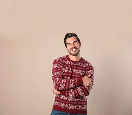 Portrait d'homme heureux en pull de Noël sur fond beige
