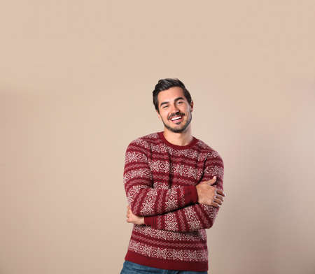 Portret szczęśliwego człowieka w świątecznym swetrze na beżowym tle