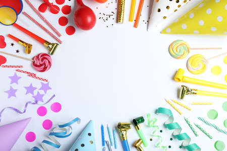 Frame made of different birthday party items on white background, top view. Space for text