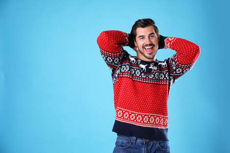 Portrait of happy young man in Christmas sweater on light blue background. Space for text