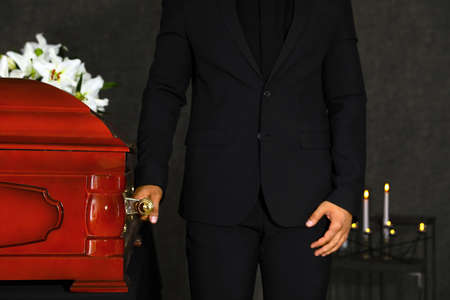 Young man carrying wooden casket in funeral home, closeup