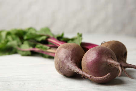 Bunch of fresh beets with leaves on wooden table against white background, closeup. Space for text