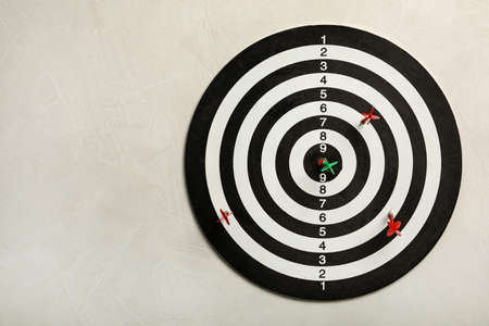Dart board with color arrows on light stone background, top view. Space for text