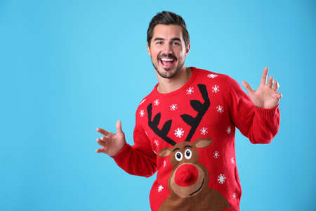 Portrait of happy young man in Christmas sweater on light blue background