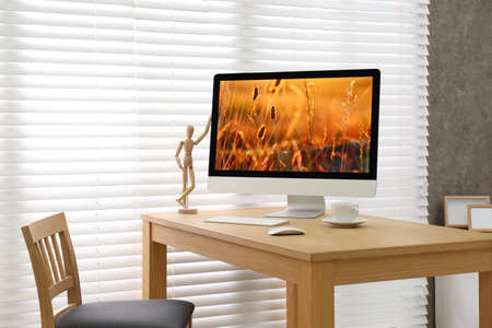 Modern PC on table near window with blinds in room