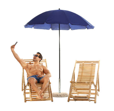 Young man taking selfie on sun lounger under umbrella against white background. Beach accessories Standard-Bild
